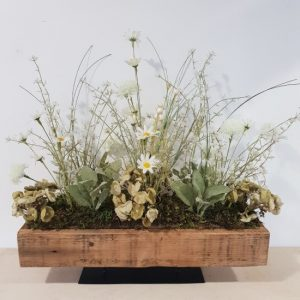 Hand arranged wooden trough of faux wildflowers